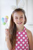Portrait of a pretty little girl wearing bunny ears holding Easter eggs