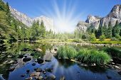 The magnificent Yosemite Valley. The huge granite monolith El Capitan and the shining sun reflected in the smooth waters of the river Mersed