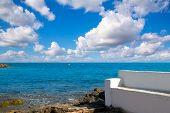 Torrevieja Alicante white bench in the shore rocks of Mediterranean sea