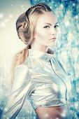 Close-up portrait of a beautiful young woman in silver latex costume with futuristic hairstyle and make-up. Sci-fi style.