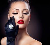 Beauty Fashion Glamour Girl Portrait over black background. Vintage Style Girl Wearing Gloves. Jewel