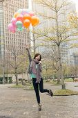 Happy smiling Asian woman holding balloons at street, Taipei, Taiwan, Asia.