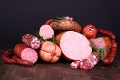 picture of sausage  - Lot of different sausages on wooden table on black background - JPG