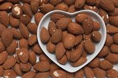 Almond nuts, healthy food ingredient in heart shape tray