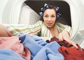 a woman reaching in the dryer for clothes
