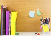 Stationery Set With Book Arrange In Row,group Of Color Pencil And Notepaper On Wooden Wall