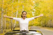 pic of open arms  - image of young happy woman in her car - JPG