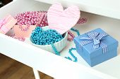 Gift boxes and beads in open desk drawer close up