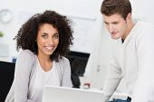 stock photo of she-male  - Beautiful African American businesswoman with a frizzy afro hairstyle smiling at the camera as she works alongside a male colleague - JPG