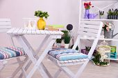 Garden chairs and table with flowers on shelves on white background