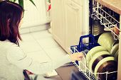 Young woman in kitchen doing housework. Puling out dishes from dishwasher