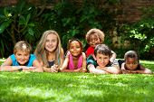 Diverse Group Of Kids Together In Garden.