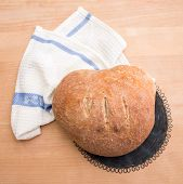 image of home-made bread  - Fresh home baked loaf of bread on wooden table with white tablecloth and black vintage drying rack - JPG