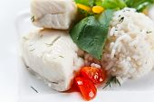 picture of halibut  - Halibut with greens rice and vegetables on white plate