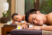 Indonesian Asian couple man and woman in wellness beauty spa having aroma therapy massage with essen