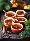 Apple cider with cinnamon sticks and anise star in apple cups