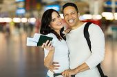 adorable couple with flight tickets and passports at airport
