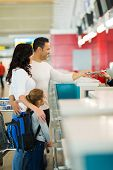 image of over counter  - family checking in at airline counter in airport - JPG