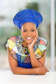 image of traditional attire  - smiling african woman in traditional clothes relaxing at home - JPG