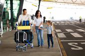 cheerful young family at airport with a trolley full of luggage