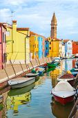 Color houses with boats on Burano island near Venice , Italy