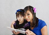 picture of sulky  - Cute child and young woman reading a story - JPG