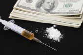 Syringe, cocaine and dollars on a black background