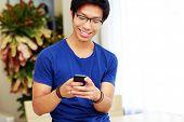 Smiling asian man using smartphone
