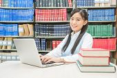 Asian Student Using Laptop Computer In University Library