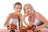 Mother And Daughter Eating Pies