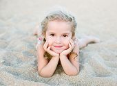 Happy Little Girl Lying On The Sand