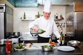 Image of male chef pouring olive oil into vegetable salad in the kitchen