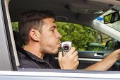 stock photo of blood drive  - Youg man in car blowing into breathalyzer - JPG