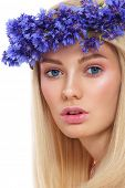 Young beautiful fresh girl with wreath of blue cornflowers on her head over white background