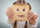 Little girl holding in front of his face a happy slice of bread