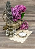 Lilac Flowers And Antique Inkwell On Wooden Background