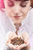 Young Caucasian Girl Holding Heap Of Unbroken Coffee Beans And Breathing In Aroma. Lighting Effects