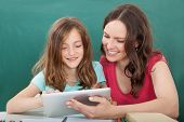 Woman Assisting Girl In Using Digital Tablet