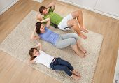 Family Doing Situps On Rug At Home