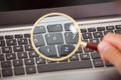 Hand Analyzing Laptop With Magnifying Glass