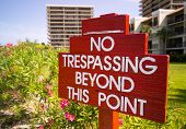 No Trespassing Sign In Red By Flower Gardens