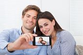 Couple Taking Self Portrait Through Smartphone At Home