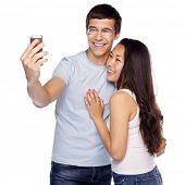 Young smiling interracial couple taking selfie on mobile phone isolated on white background