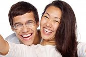 Close-up portrait of young smiling interracial couple taking selfie isolated on white background