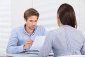 Businessman Checking Resume Of Female Candidate During Meeting