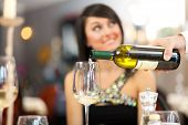 picture of waiter  - Waiter pouring white wine to a beautiful woman - JPG