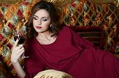 Sensual woman with a red wine glass on a magnificent sofa