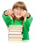 Cute little girl is reading a book and showing thumb down sign using both hands, isolated over white
