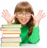 Cute little girl is reading a book while wearing glasses and showing funny grimace, isolated over wh