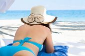 Young Woman In Sunhat Relaxing At Beach